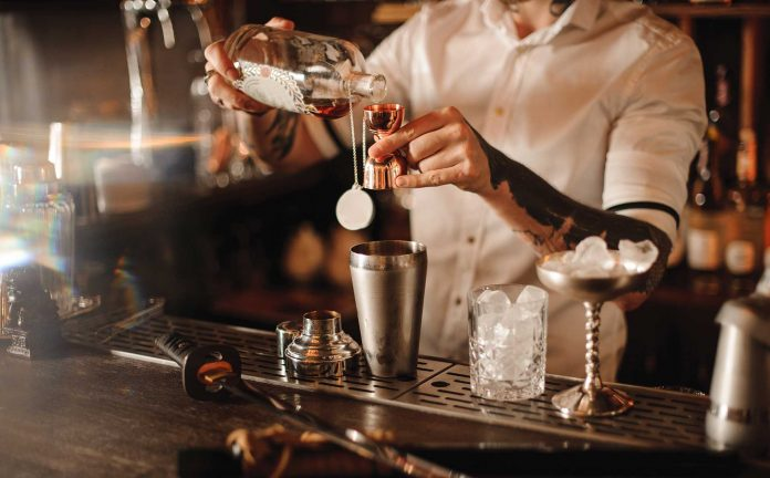 Here is a picture of a bartender pouring a drink at the bar.