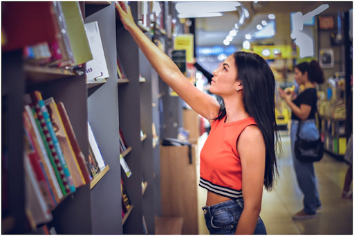 College student buying new expensive textbooks from the campus bookstore